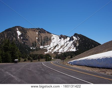 The Rim Road around Crater Lake in Southern Oregon leads to a mountain that still has snow on a sunny summer afternoon.