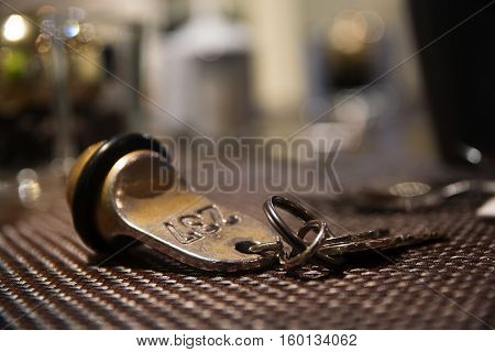 Old hotel room key from brass with the number 237 blurred background with copy space