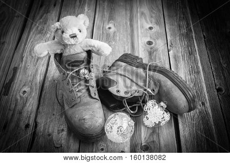horizontal black and white image of a pair of old worn out work boots with a little teddy bear sitting in one boot and two clear glass Christmas ornaments on a rustic wood plank floor with a vignette.