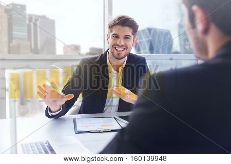 Double exposure of Two happy young businessmen sitting and working on business meeting in office