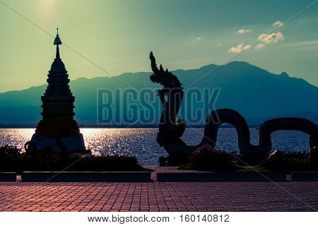 Silhouette photography of serpent (King of Nagas) statue and pagoda at riverside in evening on beautiful landscape background (Sunlight reflection on water surface and mountain)