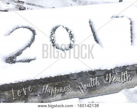 Happy New Year 2017 card or background with 2017 written in fresh snow, room for copy space and lettering with common New Years Wishes