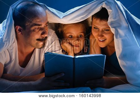 Young man and woman and theirs daughter lying down on white sofa. reading book. and blue night light background