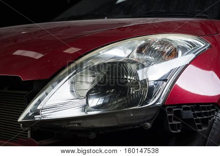 Auto body repair series : Closeup of red car headlights waiting for repaint