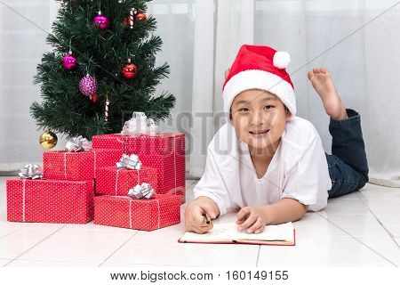 Happy Asian Chinese Little Boy Writting Book Beside Christmas Presents