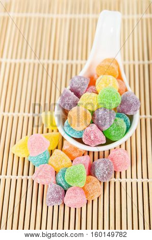 Colorful candies jelly sugar in white spoon on bamboo mat.