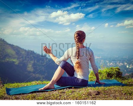 Hatha yoga - fit woman doing yoga asana Parivrtta Marichyasana (or ardha matsyendrasana) -  seated spinal twist outdoors in mountains in the  morning. Vintage retro filtered hipster style image.