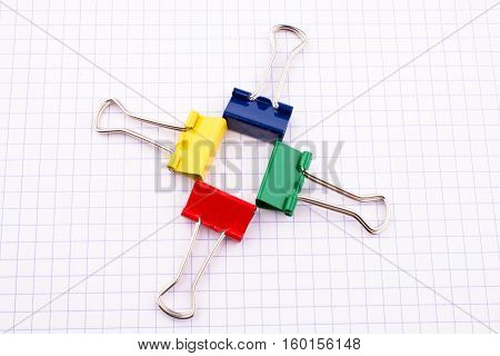 Four Colorful Clips Placed On  White Checked Paper