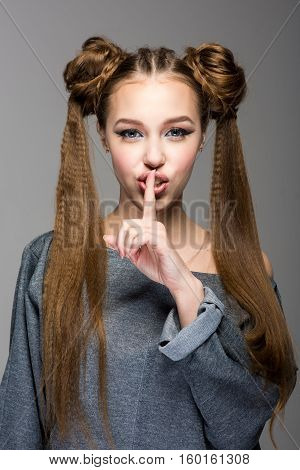 Portrait of a beautiful young girl with two ponytails, holding finger to her lips in a gesture for silence. Isolated on gray background