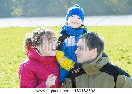 Outdoor seasonal family portrait of three happy people in sunny park