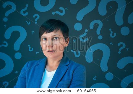 Businesswoman with question marks looking for answers questioning and wondering about uncertain future in corporate business