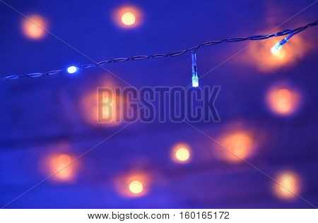 Decorative lights on blue blurred background. New Year and Christmas concept