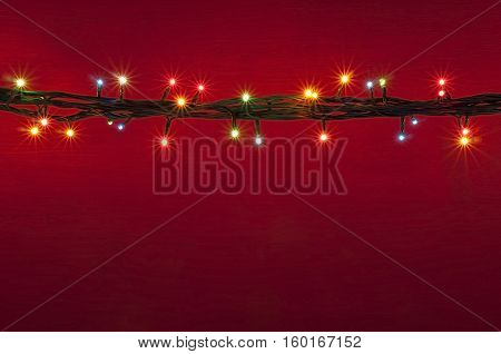 Christmas lights on red background. Multicolored lights background. Abstract light. Colorful light. background. Border multicolored light.
