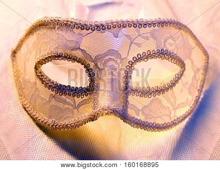 Close up of a lace carnival mask (homemade product) on evening clothes. Fashion background.
