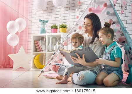 Happy loving family. Pretty young mother reading a book to her daughters indoors. Funny mom and lovely child having fun in children room.