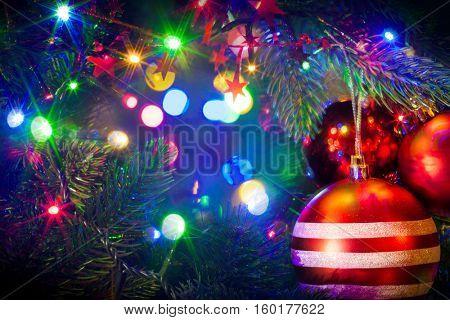 Red Christmas balls hanging on Christmas tree over light bokeh background