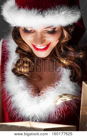 Beautiful woman in Santa Claus style costume looking into glowing Christmas gift box