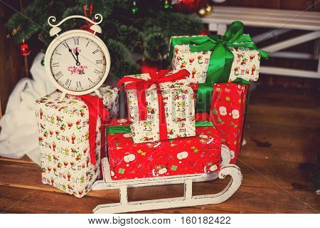 Photo of luxury gift boxes under Christmas tree New Year home decorations wrapping of Santa presents festive fir tree decorated with garland traditional tselebration
