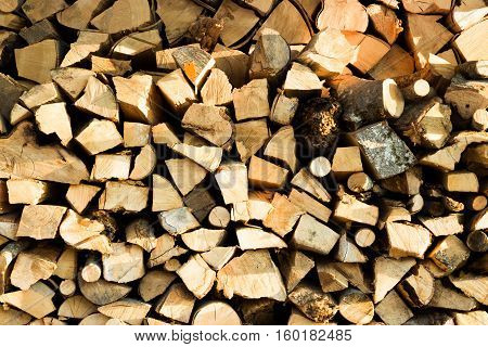 Stacked woodpile of cut and split dried logs ready to be used as natural sustainable winter fuel for household heating and energy full frame texture