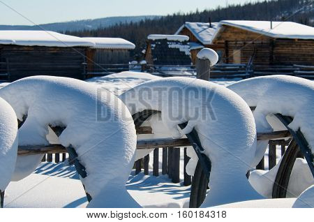 Covered with snow fence in village on sunset