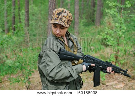 A woman soldier with a weapon. Zone of armed conflict.