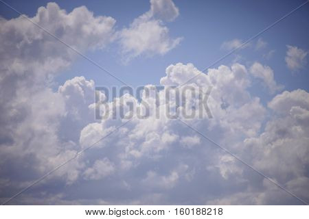 Blue and white cumulus clouds close-up and blue sky