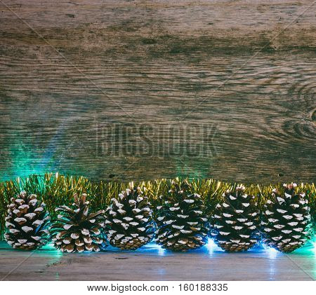 Festive Christmas background. Fir cones Golden tinsel and lights garland on a old barn boards. Tinted photo