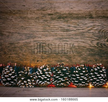 Festive Christmas background. Fir cones blue tinsel and lights garland on a old barn boards. Tinted photo