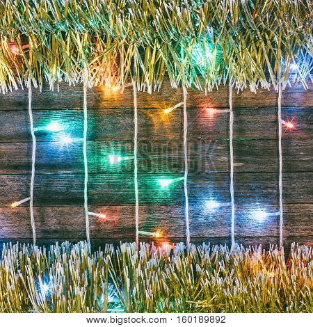 Festive Christmas background. Multicolored lights garland and gold tinsel on the old barn boards. Tinted photo