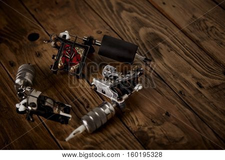 Three Tattoo Guns Arranged On A Brown Wooden Table
