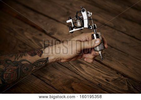 Close Up Of A Man's Hand With  Tattoo Gun