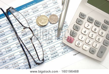 Coins and calculator with silver pen on top of financial statement