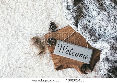 Winter homely scene, scandinavian style. Warm knit blanket and other decor on wooden tray. Craft sign board Welcome. Cafe or home interior decoration.