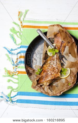 Rockfish baked in paper on a white table