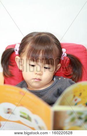 Japanese girl reading a picture book (2 years old)