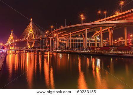 bhumibol bridge cross over river at night in thailand