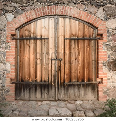 old wooden door with wrought iron elements isolated on the stone wall background