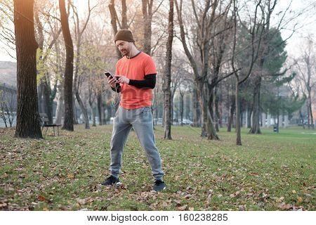 Young Man Working Out In The City Park And Using His Mobile Phone