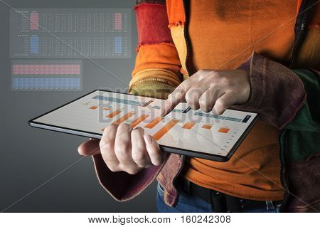 Hand touching modern tablet with financial graph. Business analysis concept.