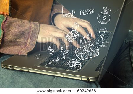 Hand typing on a laptop with business icons and symbols. Business technology internet and networking concept.