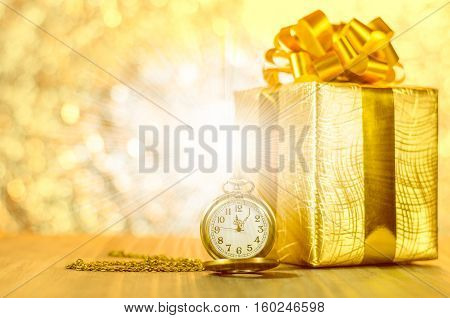 Vintage pocket watch with gold christmas gift box ribbon and bow on bokeh lights background