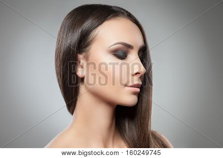 Head shot of young model with heavy make up keeping eyes closed on studio background.