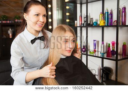 Hairdresser touching woman's hair. Horizontal indoors shot