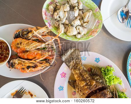 Grilled shrimps served on the table with seafood set.