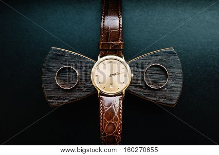 Composition of the groom's accessories on a black background. Gold watch, wooden bow tie and wedding rings