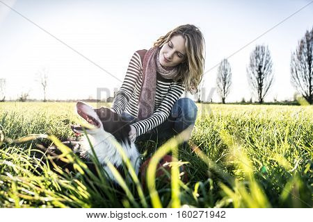 Woman playing with her border collie in the grass