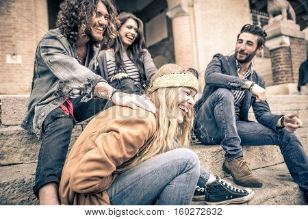 Group of four friends laughing out loud outdoor sharing good and positive mood