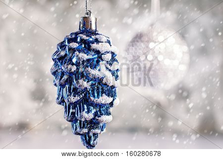 Christmas toy hanging on a thread on blurred blue background and falling snow