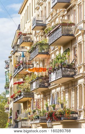 Traditional European residential house with balconys with colorful flowers and flowerpots. Kreuzberg neighborhood, Berlin, Germany,