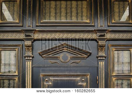 Wood carving with arch above the door in an old building.